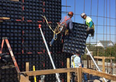 two men lifting concrete paneling